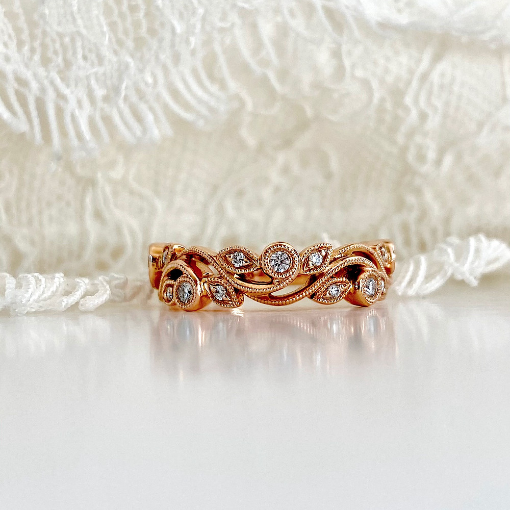 Rose gold filigree vine ring with diamonds on white lace background