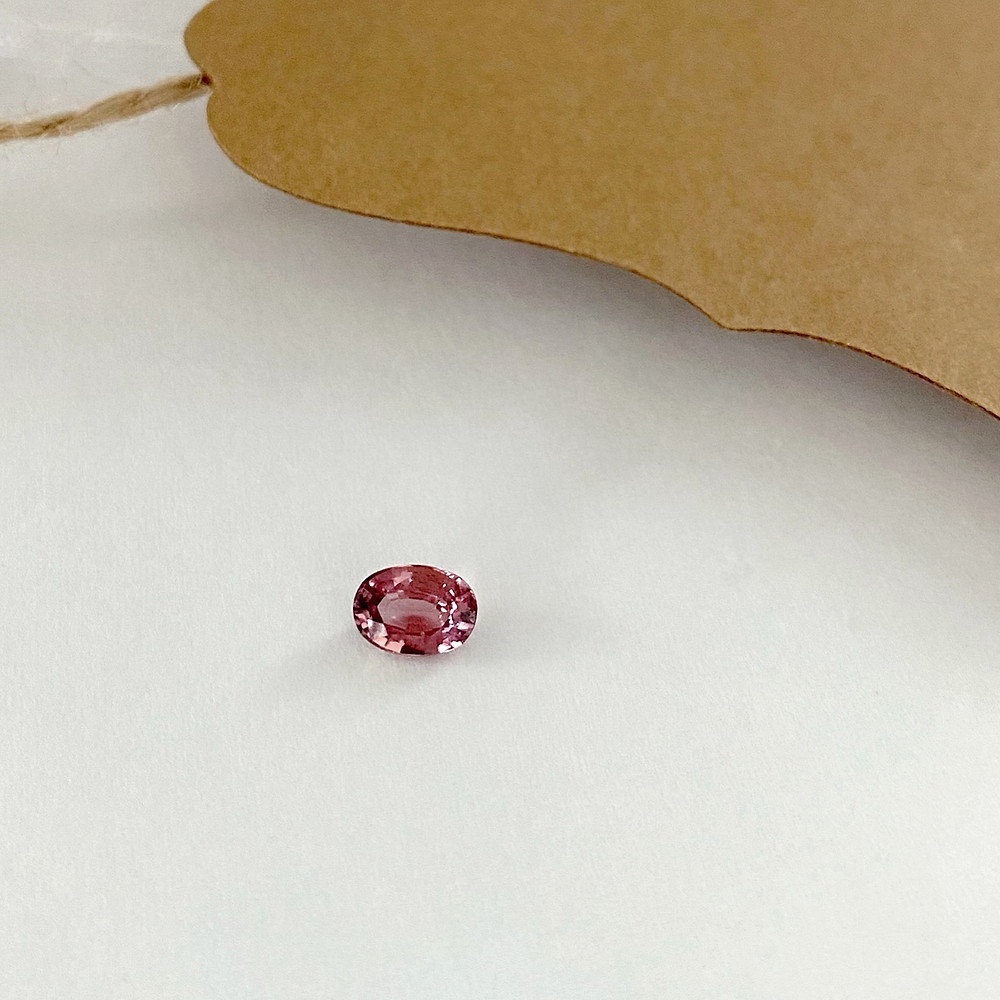 loose orangey pink oval Padparadscha sapphire on white background