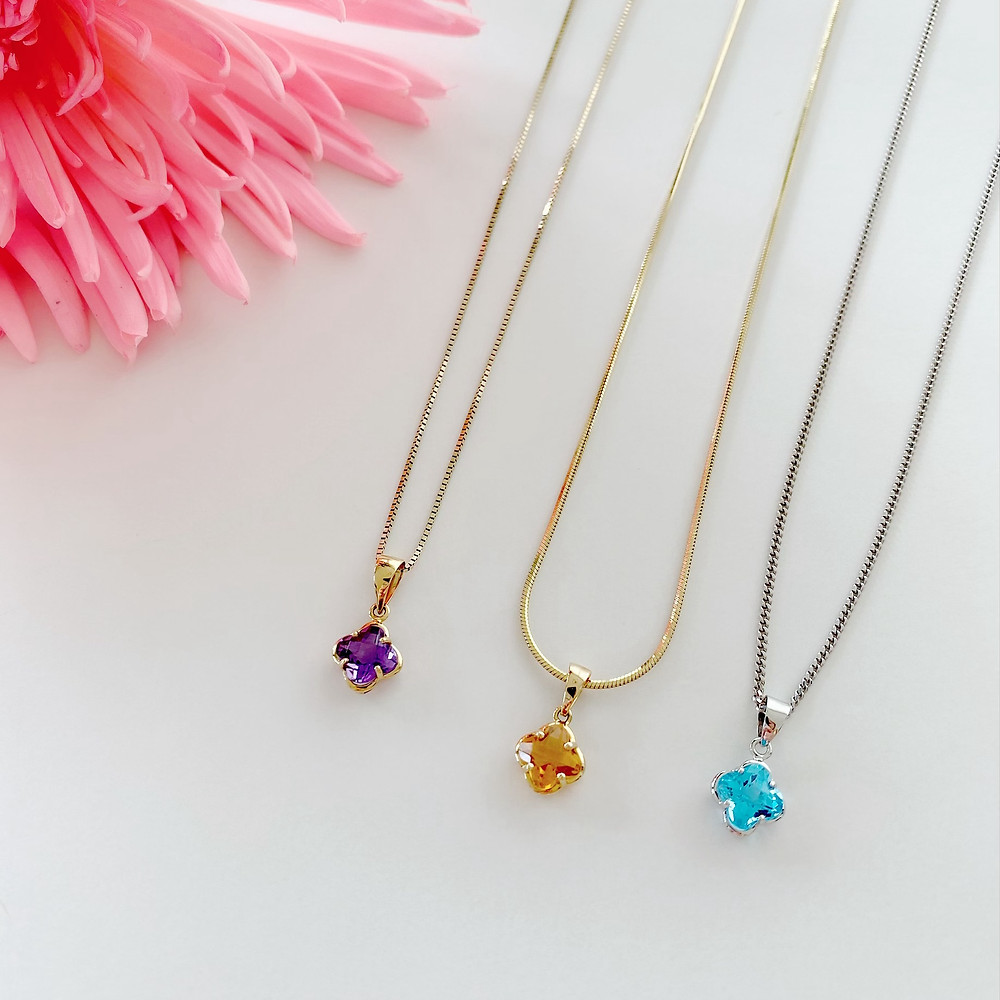 amethyst, citrine and blue topaz four leaf clover necklaces next to a pink flower on a white background