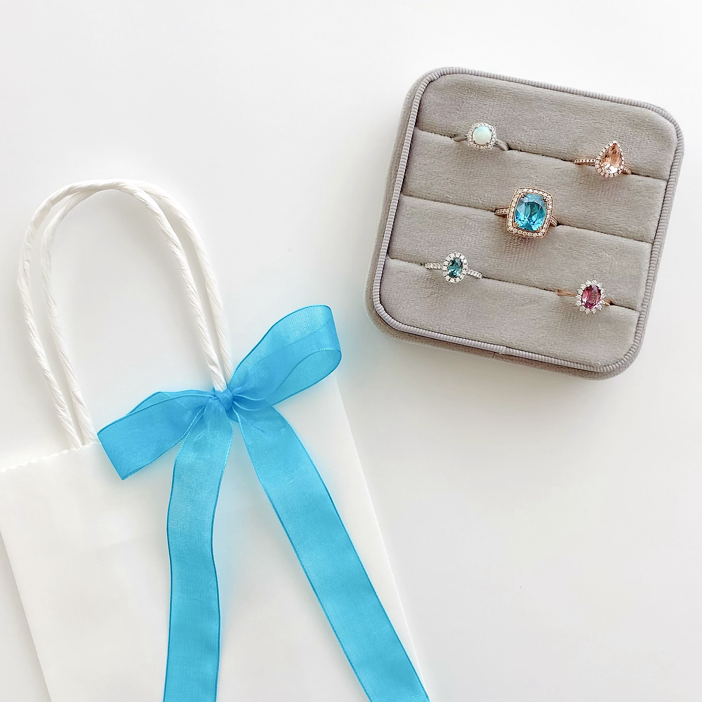 large grey velvet ring box with a selection of engagement and cocktail rings next to a white bag with blue ribbon tied in a bow