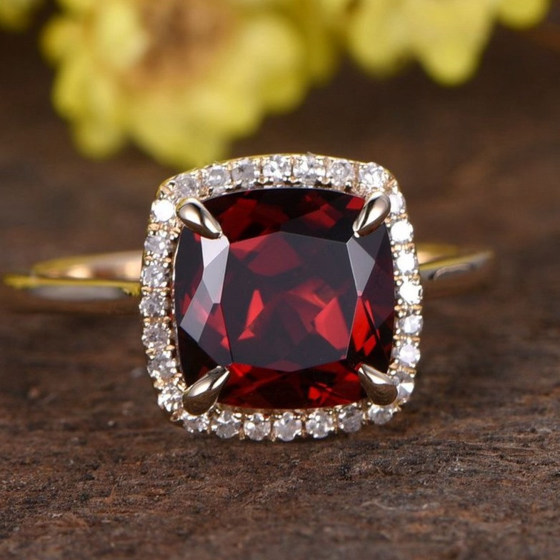 square cushion red garnet yellow gold and diamond halo ring on brown and yellow flower background
