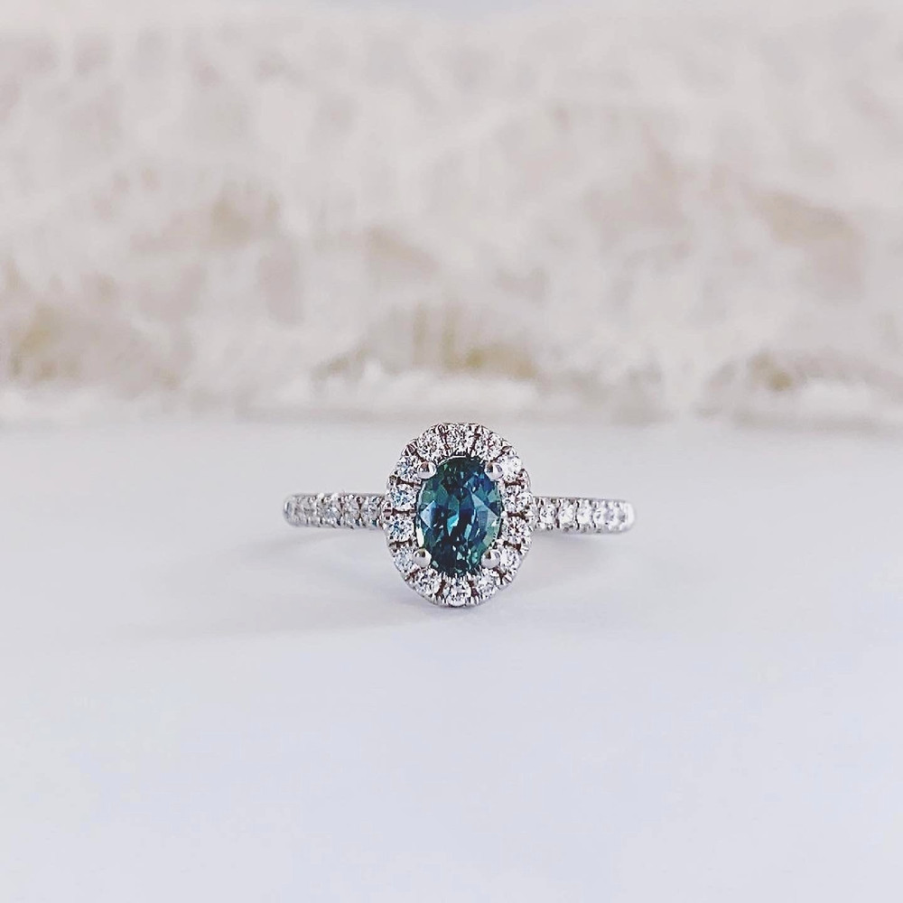 oval blue green sapphire and diamond halo white gold engagement ring on a white background