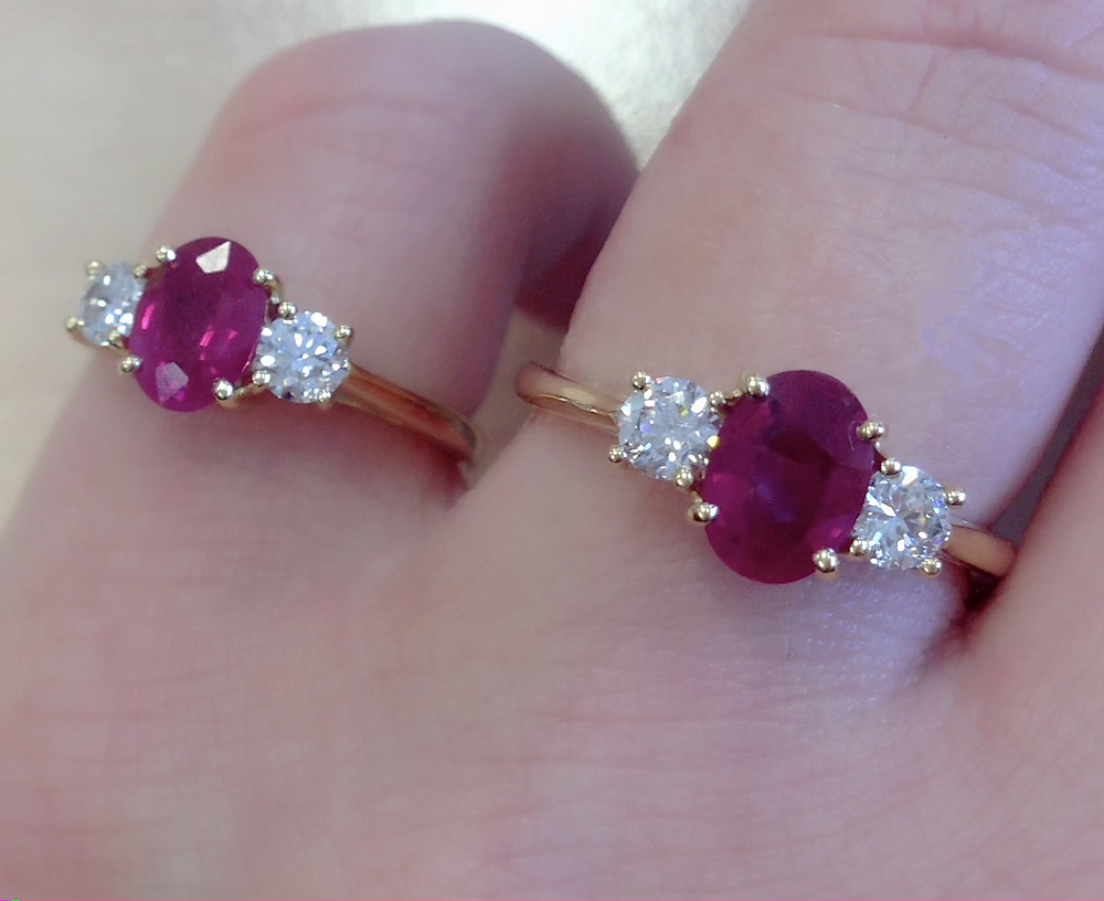 lady's hand wearing oval ruby and round diamond three stone yellow gold engagement ring