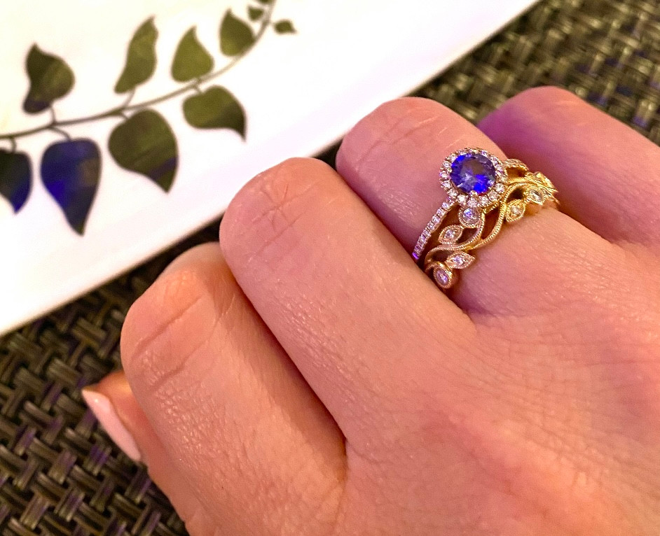 lady's hand wearing a round purple sapphire, vintage inspired, rose gold halo engagement ring and vintage inspired scroll stacking band in rose gold with diamonds, by Tsarina Gems