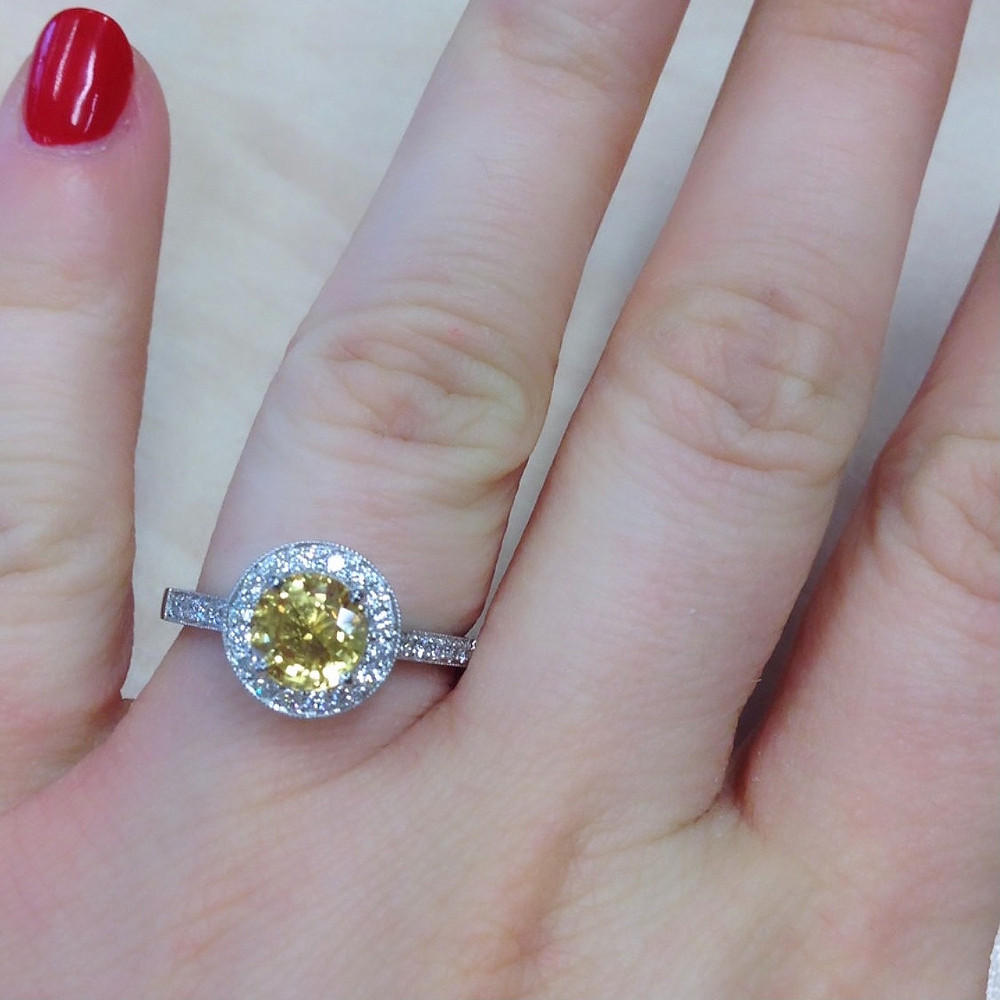 lady's hand wearing a round yellow sapphire, diamond halo engagement ring, red nails