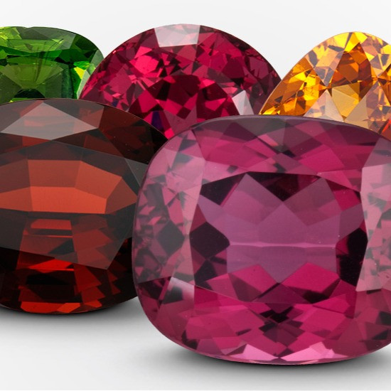 a variety of loose garnets in different shapes and colours, purple, red, yellow orange, green, on a white background