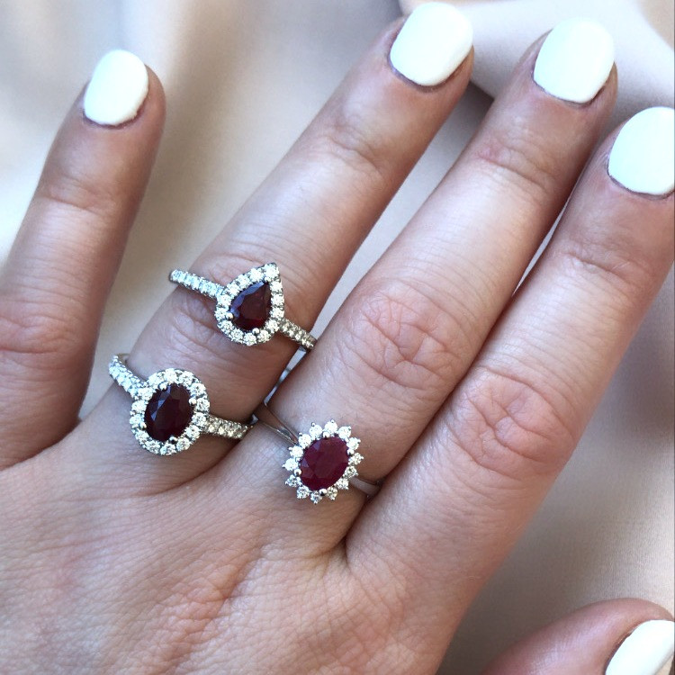 lady's hand wearing a selection of vintage inspired oval and cushion cut ruby and diamond halo white gold engagement rings