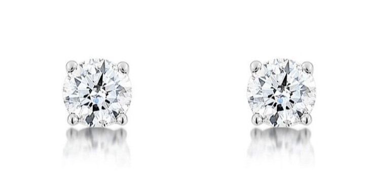 a pair of diamond stud earrings in white gold on a white background
