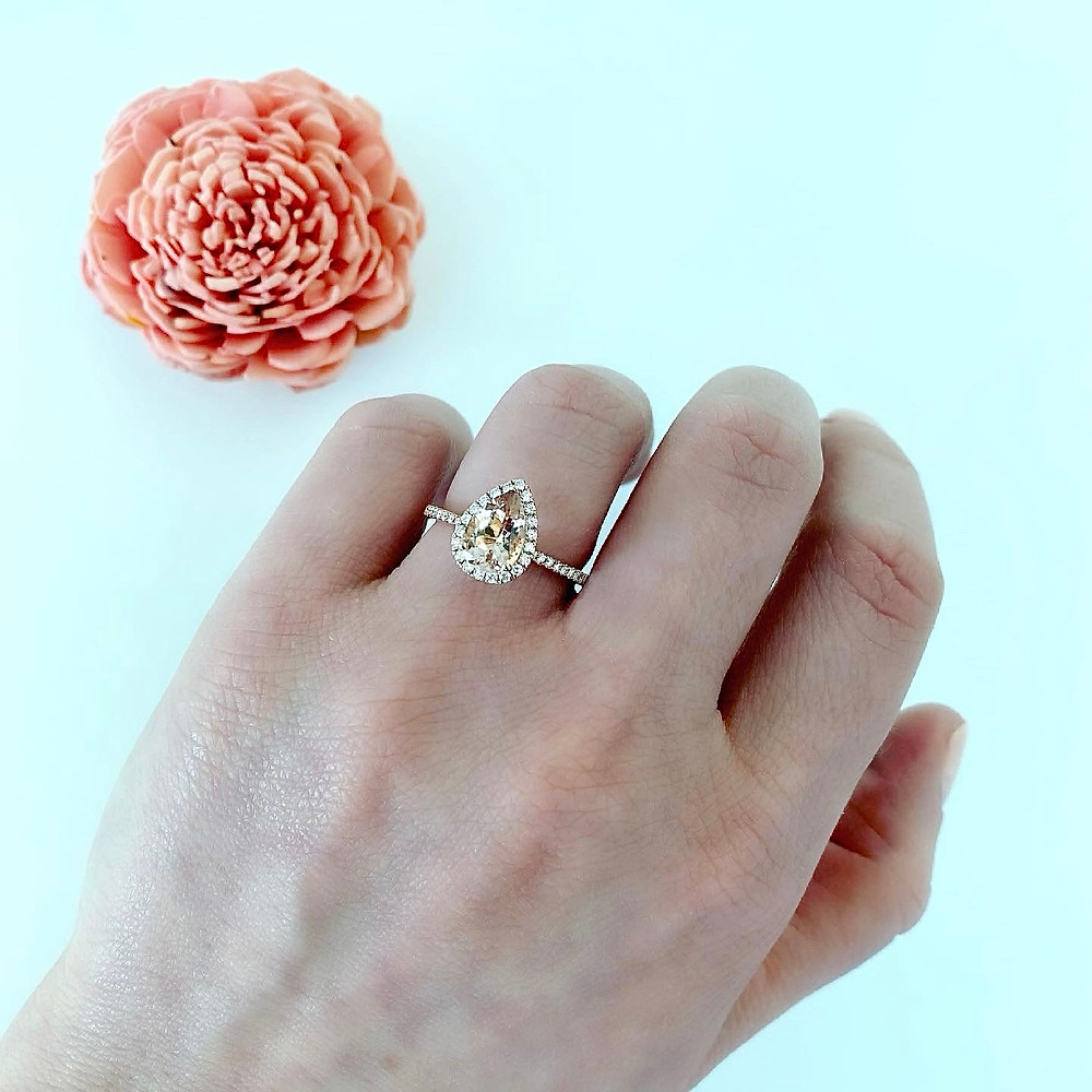 lady's hand wearing a vintage inspired pear shape morganite and diamond halo rose gold engagement ring by Tsarina Gems on a light background next to a dry pink flower