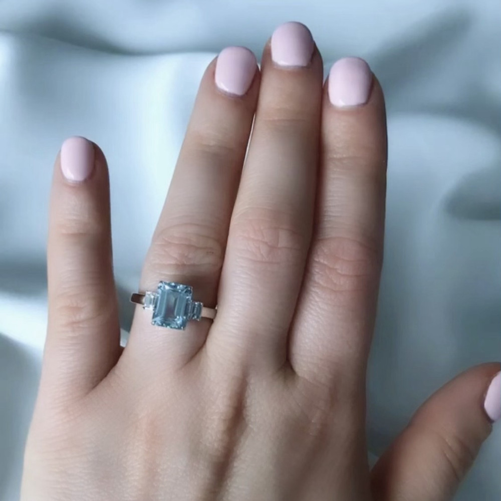 lady's hand wearing an emerald cut aquamarine ring with baguette cut side diamonds in white gold light pink manicure nail polish on a white silk background