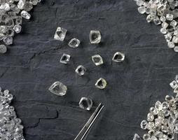 a selection of rough diamonds next to a pair of tweezers on a grey background