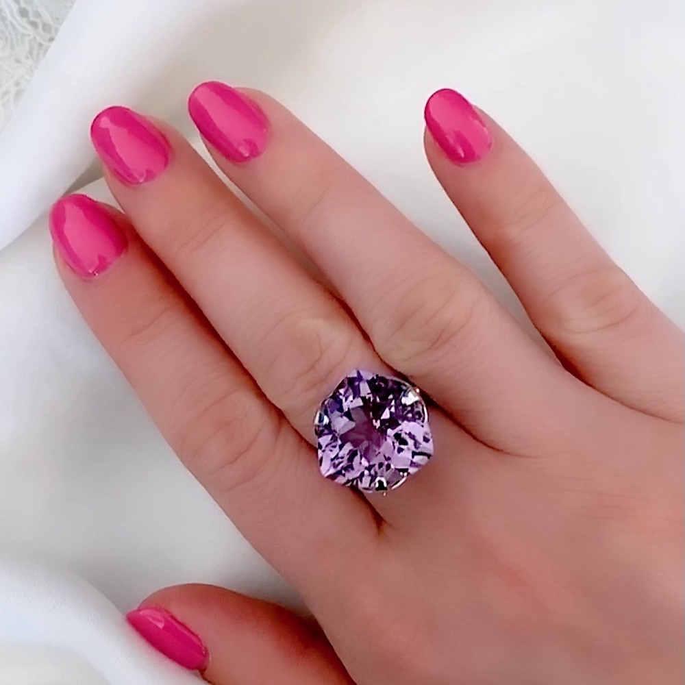 Large trilliant cut amethyst, worn on lady's hand with hot pink nails, on a white background