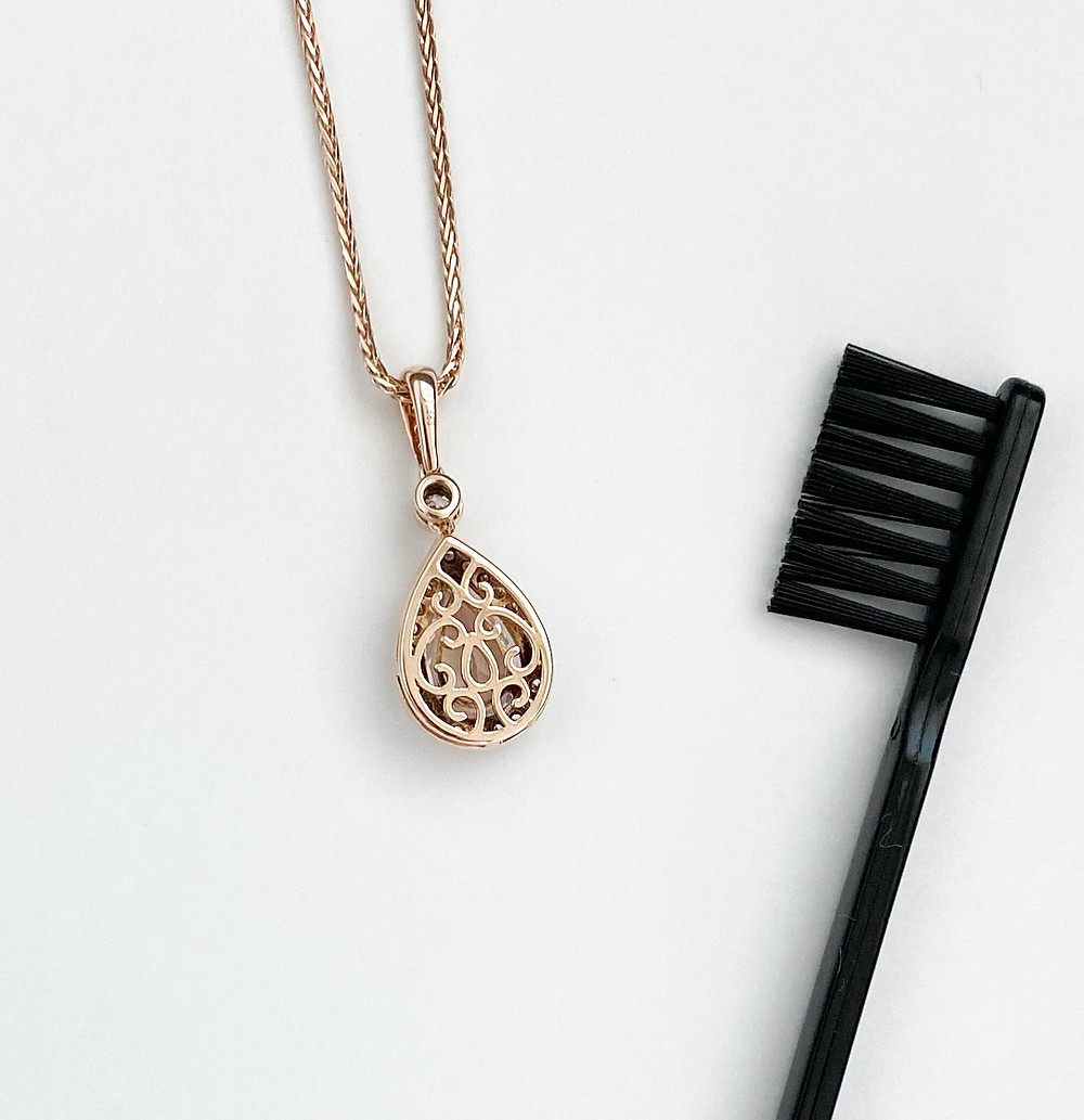 Rose gold necklace next to a small brush, jewellery cleaning tools