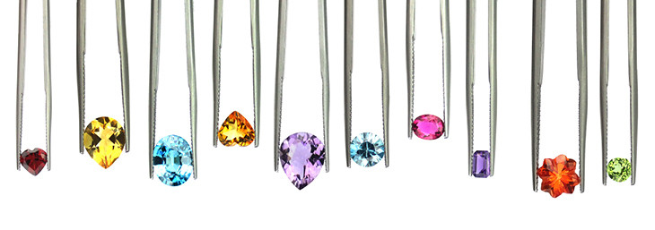 variety of coloured gemstones of different colours, shapes, sizes held in tweezers on a white background