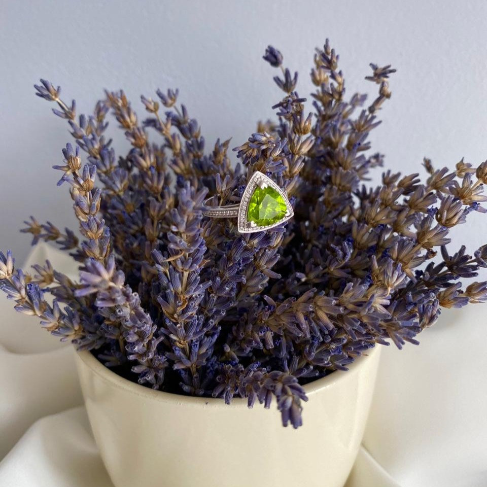 trilliant cut peridot and diamond halo white gold ring on a lavender plant
