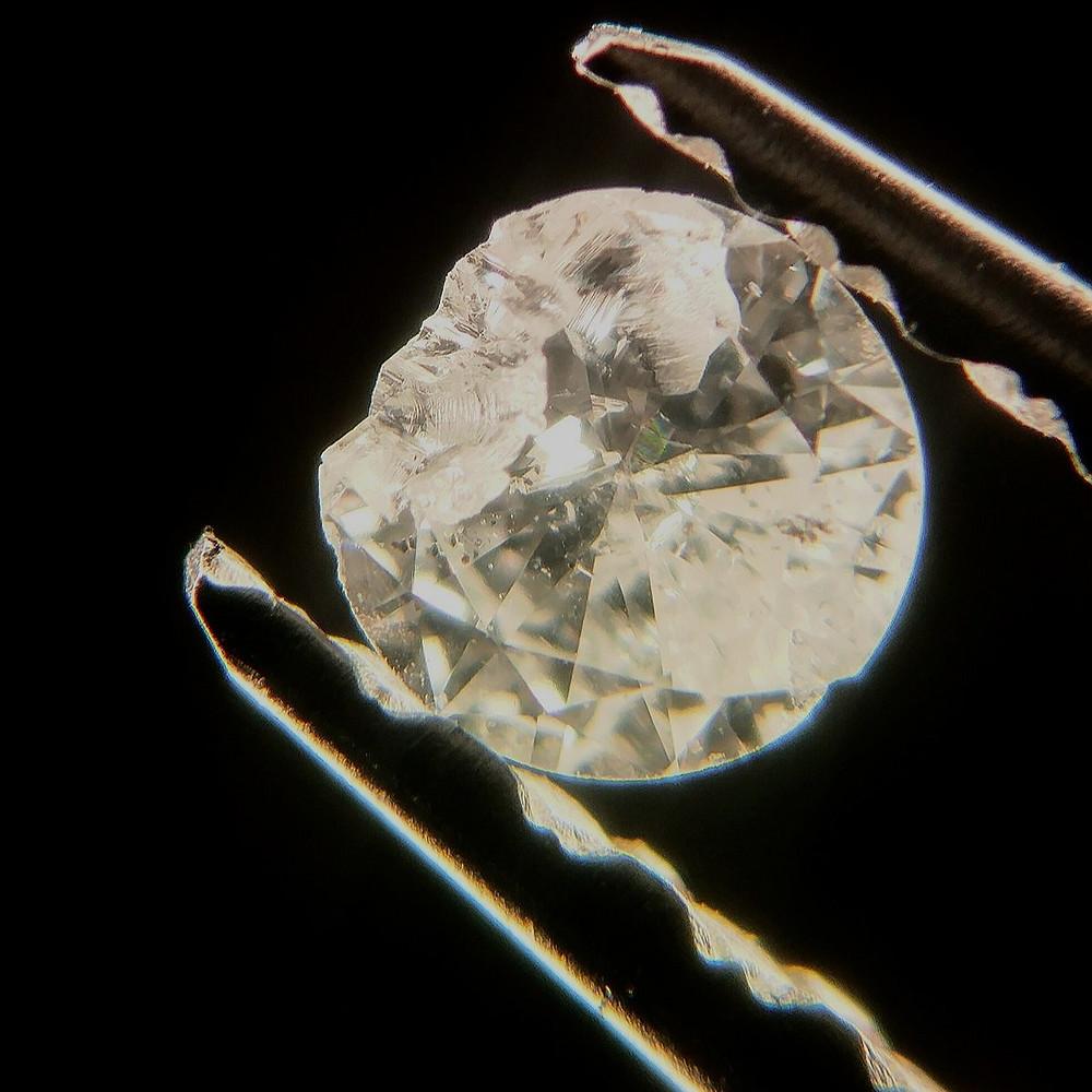 Broken diamond held in tweezers on a black background