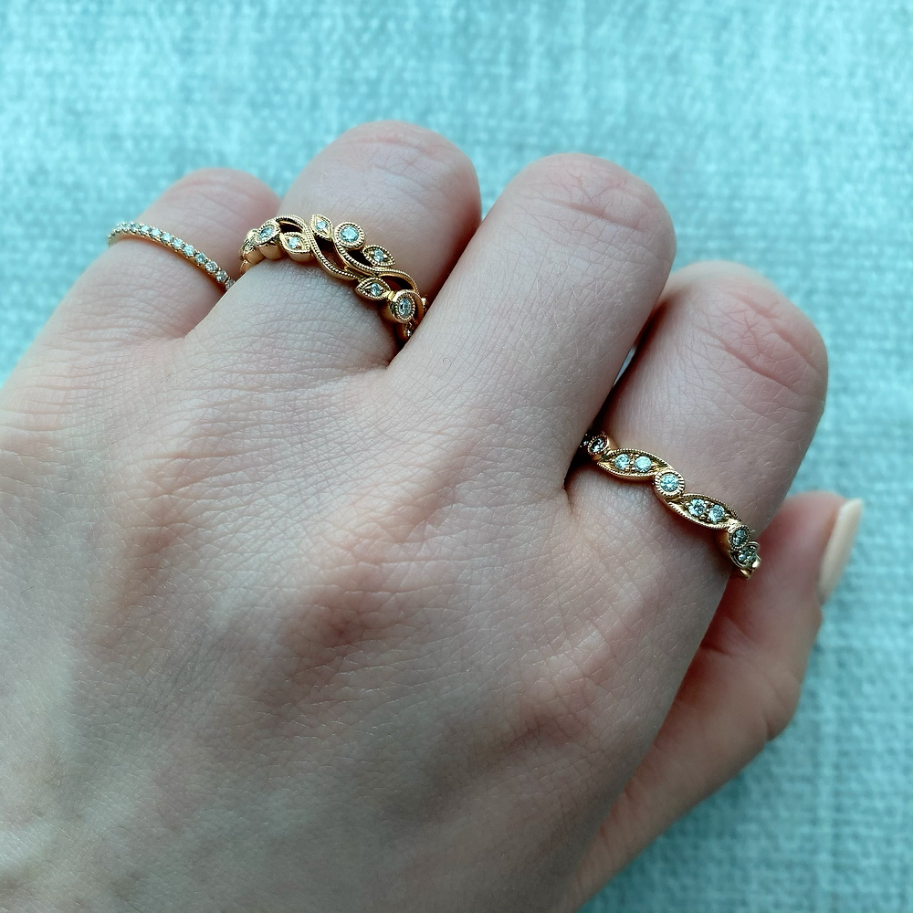 Lady's hand wearing a combination of vintage inspired rose gold and diamond stacking ring stacking bands pinkie ring by Tsarina Gems on a light blue background