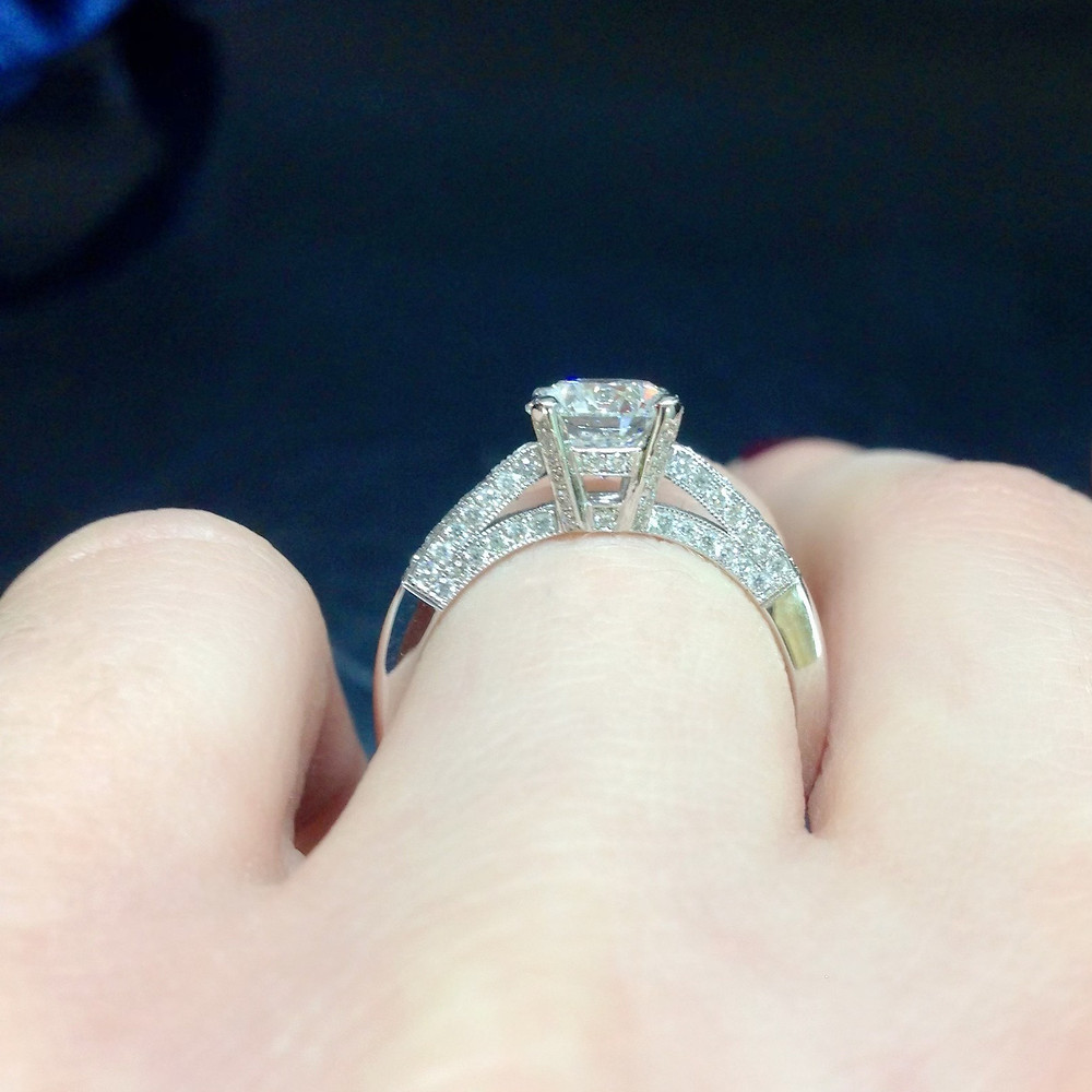 profile side view of round brilliant diamond engagement ring covered in diamonds