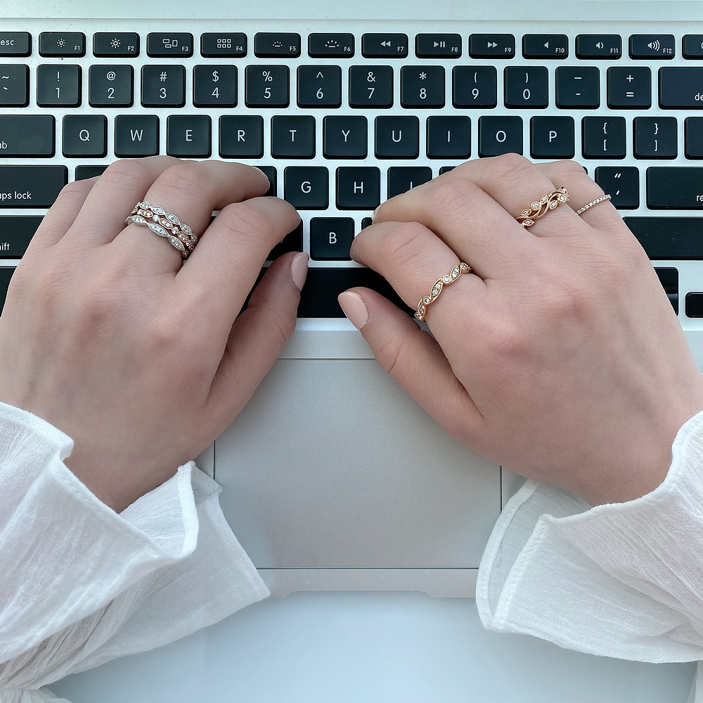 Lady's hand wearing multi coloured diamond stacking rings and typing on a laptop