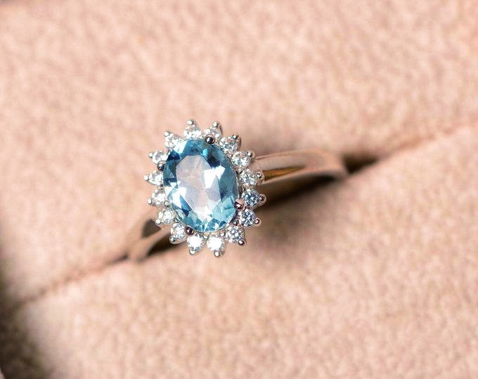 oval aquamarine diamond halo white gold engagement ring cocktail ring in a velvet beige ring box