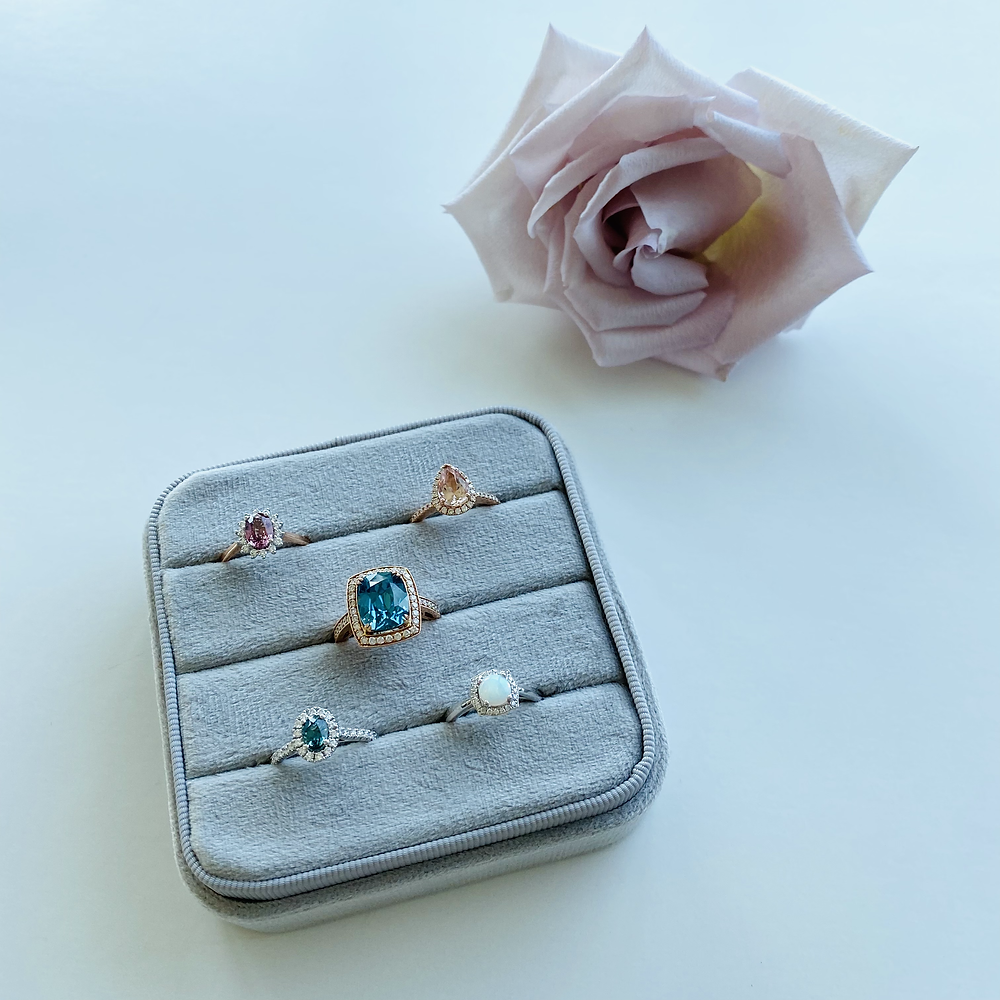 Large grey velvet ring box with engagement rings next to a pink rose