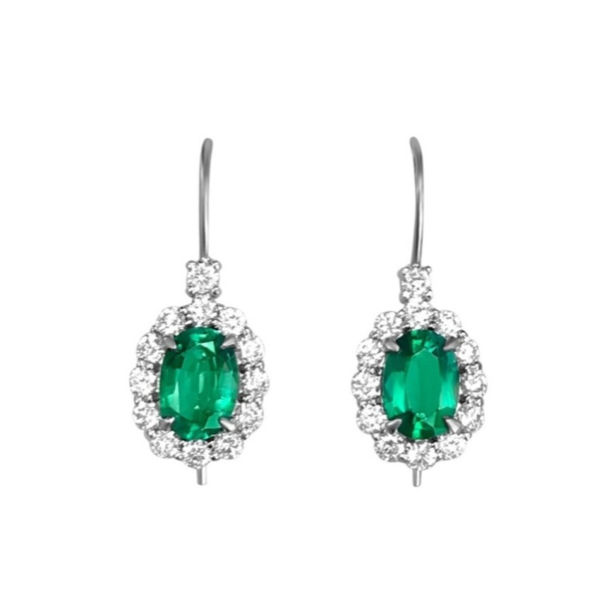 a pair of vintage inspired oval emerald and diamond halo earrings in white gold on a white background