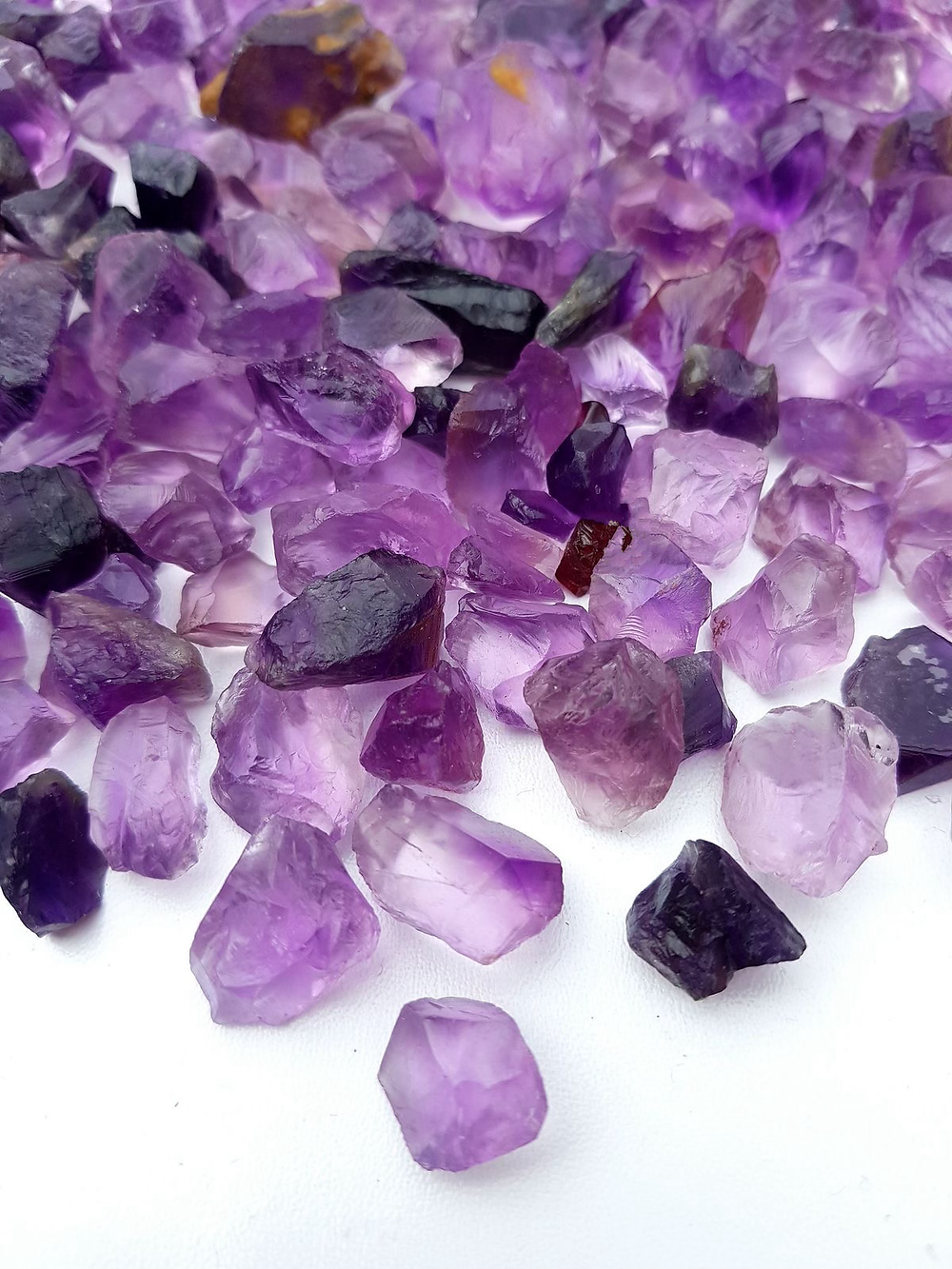 selection of amethyst rough crystals of different shape and size light and dark on white background
