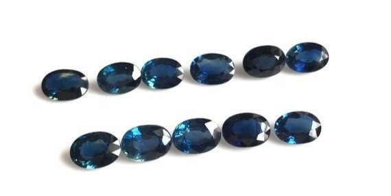 oval dark blue sapphires lined up in a row