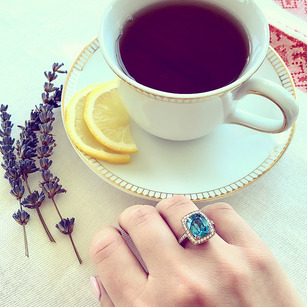 Lady's hand wearing a large cocktail ring, cushion cut blue zircon, diamond halo in rose gold, next to a cup of tea and saucer, lemon slices, dry lavender, on a white and red table cloth