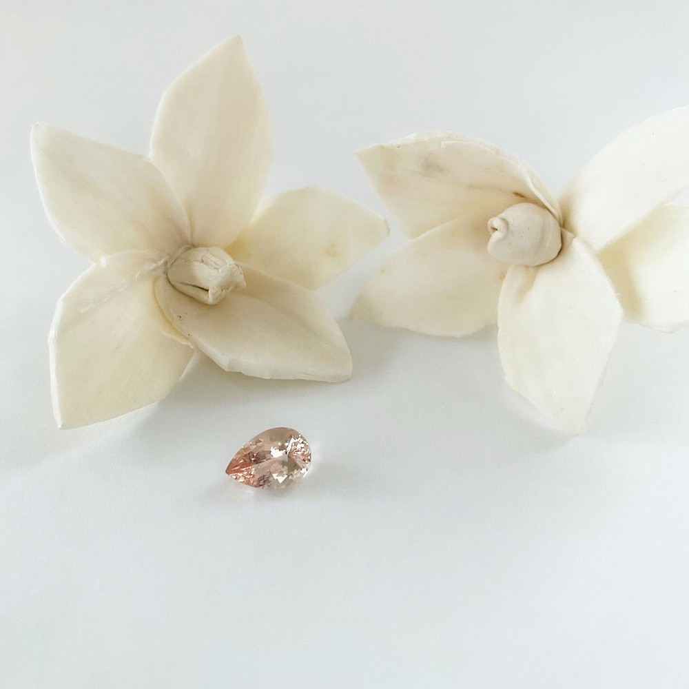 loose pear shape morganite next to dry white flowers