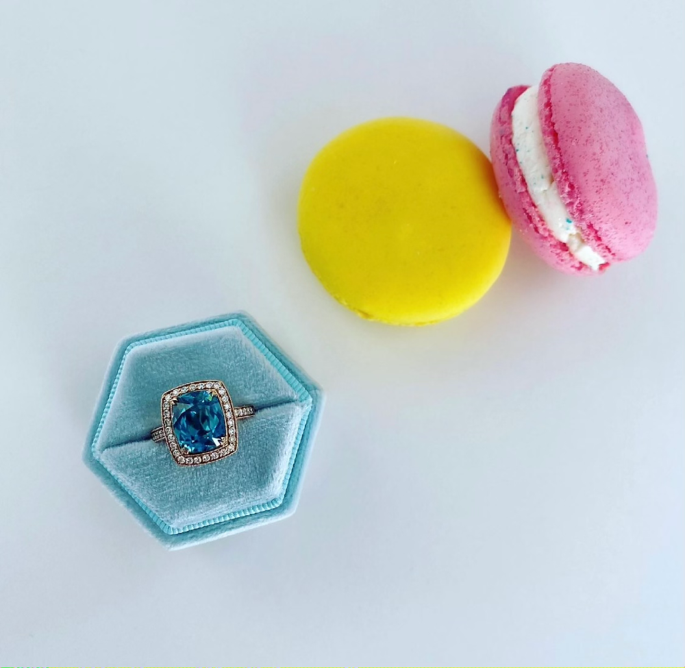 cushion shape blue zircon rose gold cocktail ring in an light blue hexagonal ring box next to yellow and pink macarons