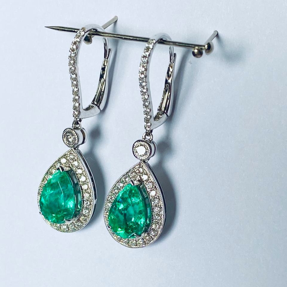a pair of pear shape emerald and diamond white gold drop earrings on a light blue background