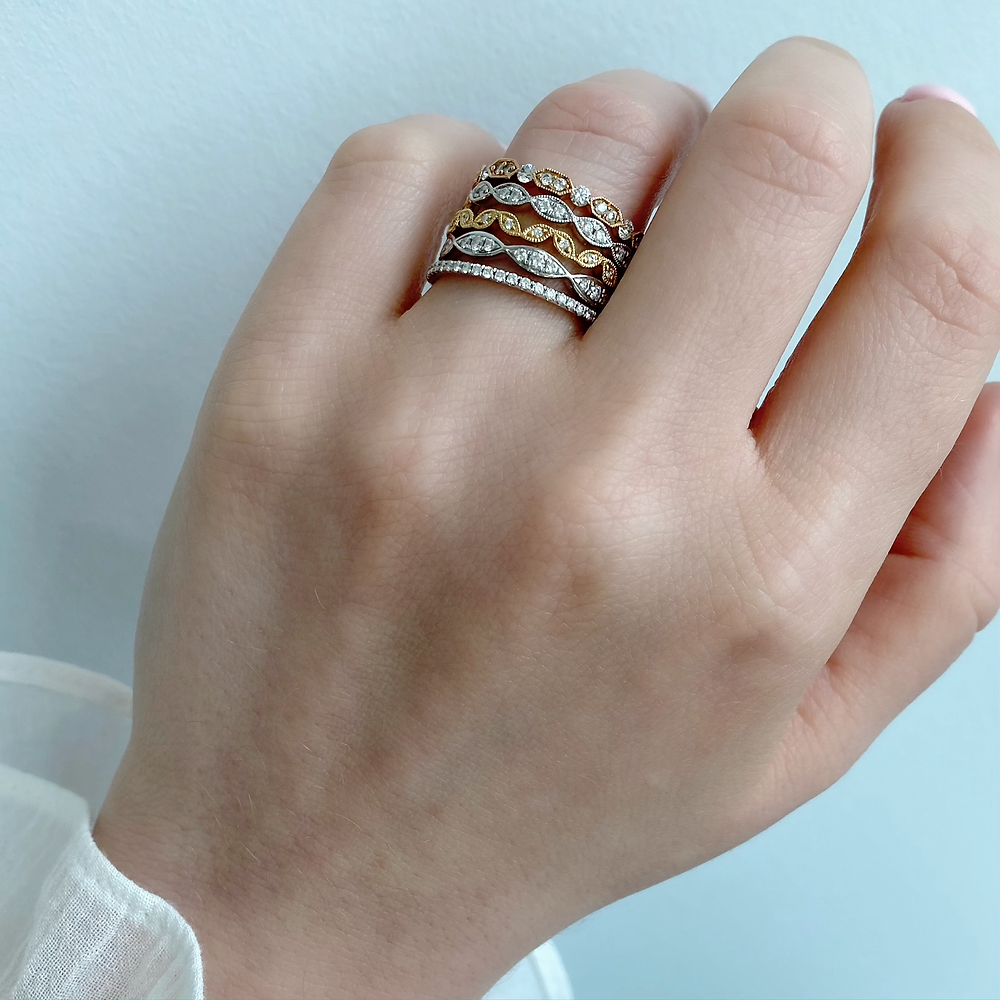 Lady's hand wearing a stack of multi coloured diamond stacking rings on her ring finger