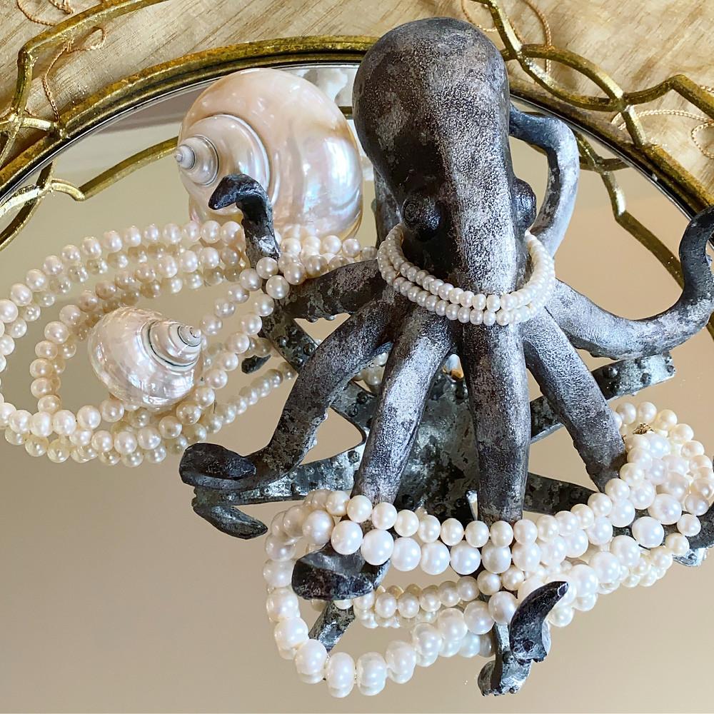 strands of pearls wrapped around a decorative octopus on a mirror tray next to decorative shells on a coffee table