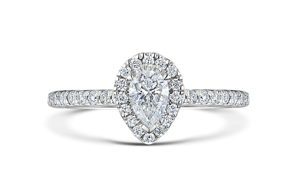 a pear shape diamond engagement ring, diamond halo, white gold, on a white background