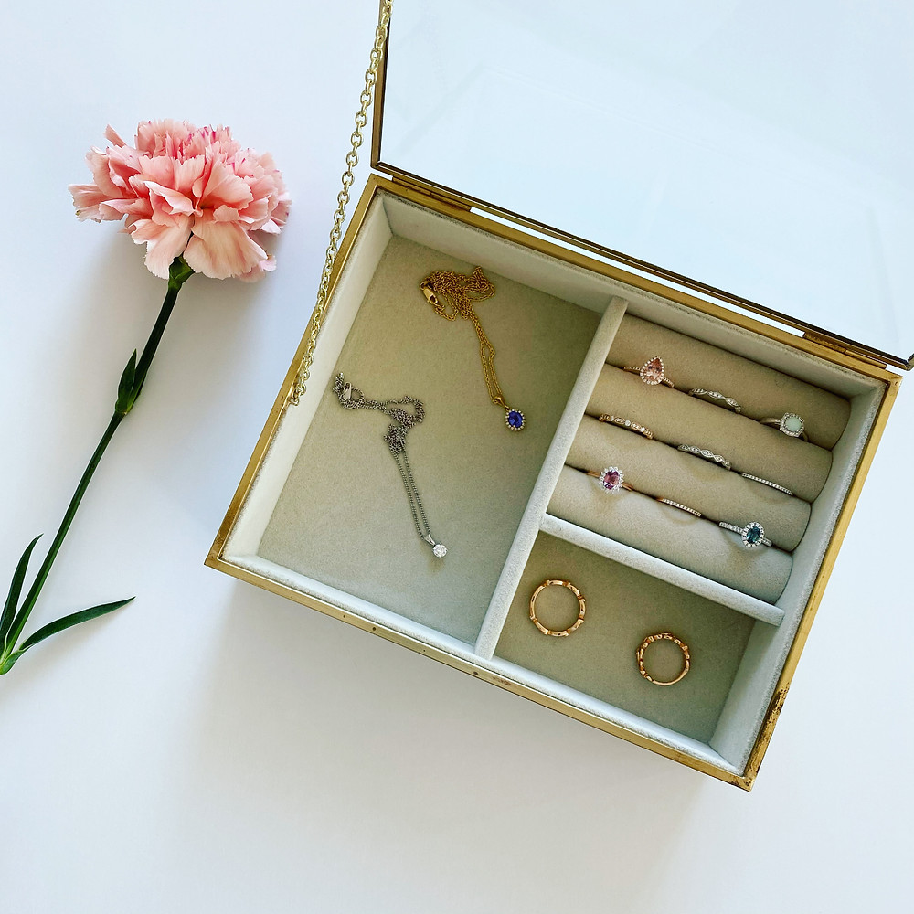 a yellow gold and glass jewellery box containing jewellery pendants and rings next to a peach carnation flower