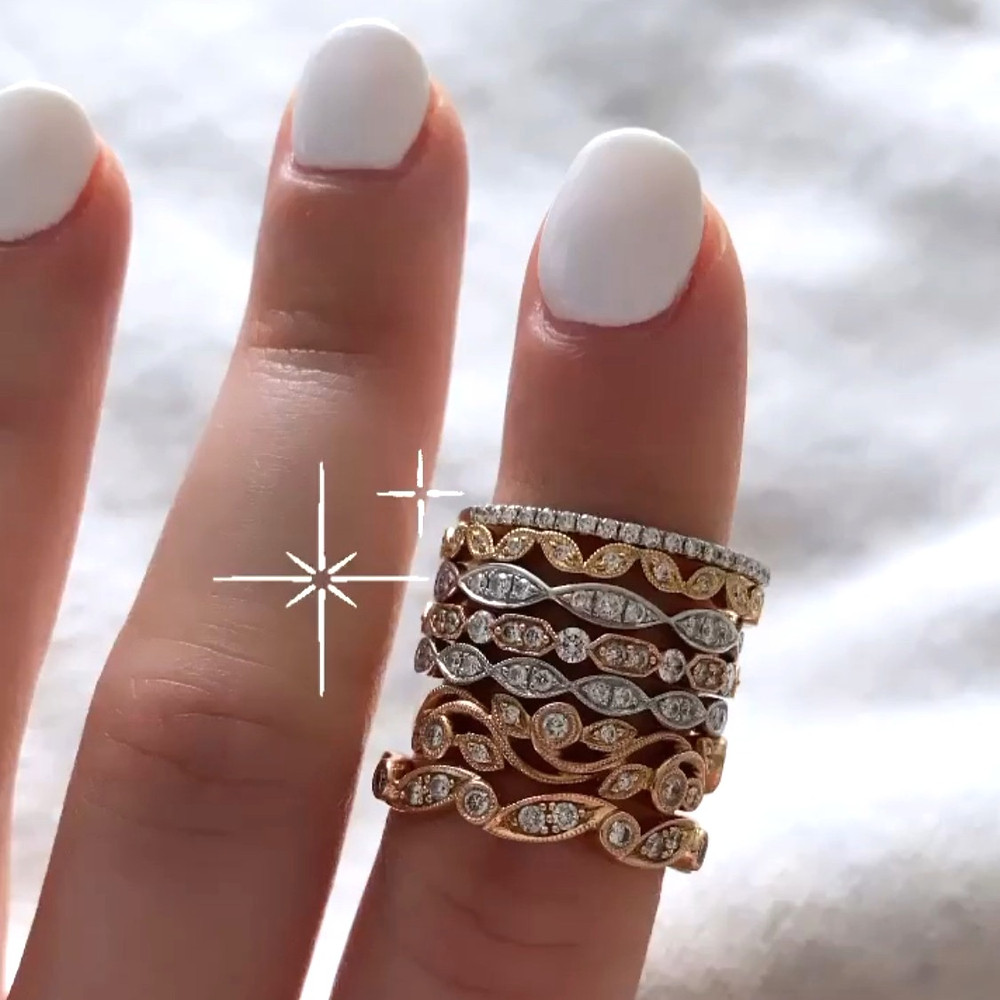 Selection of vintage inspired diamond stacking bands in rose, white and yellow gold, by Tsarina Gems, ring stack on a lady's finger with white nails