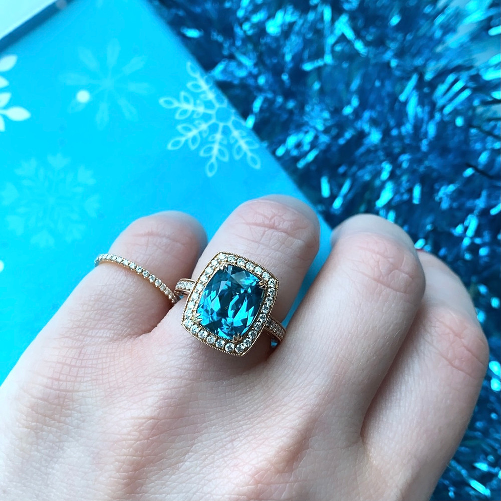 large elongated cushion cut blue zircon cocktail ring vintage inspired rose gold ring with filigree and diamond halo rose gold stacking band pinkie ring with diamonds on hand Christmas white and blue decor gift wrapping blue tinsel background by Tsarina Gems