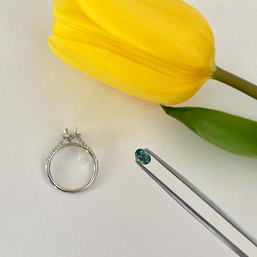 loose oval blue green teal sapphire held in tweezers, white gold semi mount ring, next to a yellow tulip, on a white background
