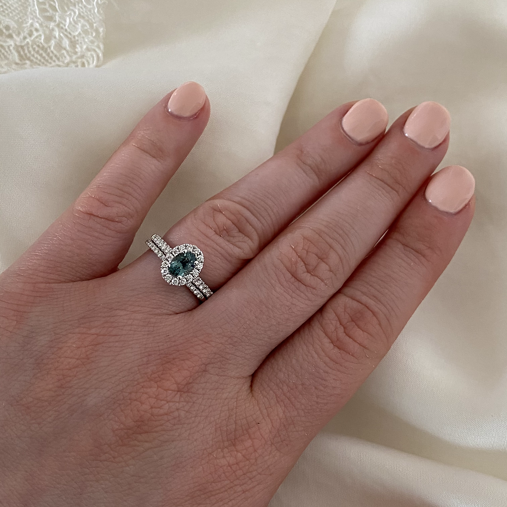 lady's hand wearing oval blue green sapphire and diamond halo white gold engagement ring, wedding band, bridal set,  teal sapphire engagement ring, mermaid sapphire, peacock sapphire, on a white silk background, by Tsarina Gems, neutral light pink nail polish