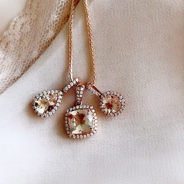 pear shape, cushion and round morganite and diamond halo necklace on a light pink silk background