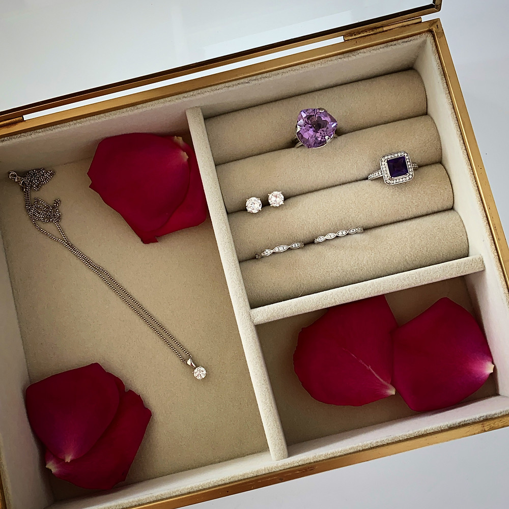 rose gold and beige glass jewellery box containing hot pink red rose petals, square dark purple amethyst in white gold diamond halo ring, large trilliant light amethyst white gold ring, diamond solitaire white gold pendant and stud earrings, diamond stacking rings