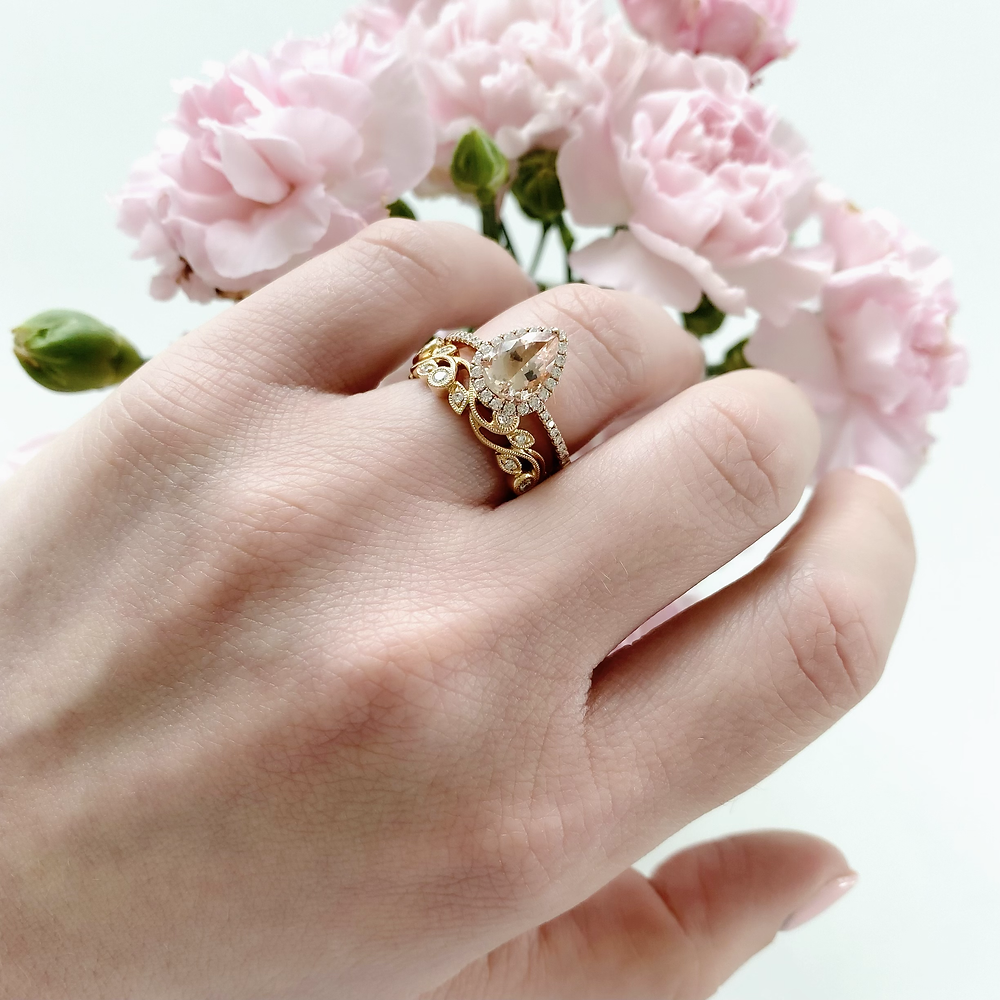woman's hand wearing a pear shape morganite and diamond halo rose gold engagement ring bridal set next to pink carnations