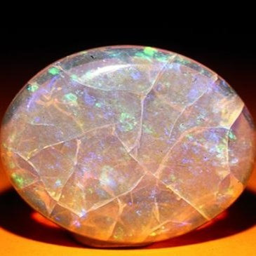 white oval opal showing cracks, fractures and crazing showing a play of colour
