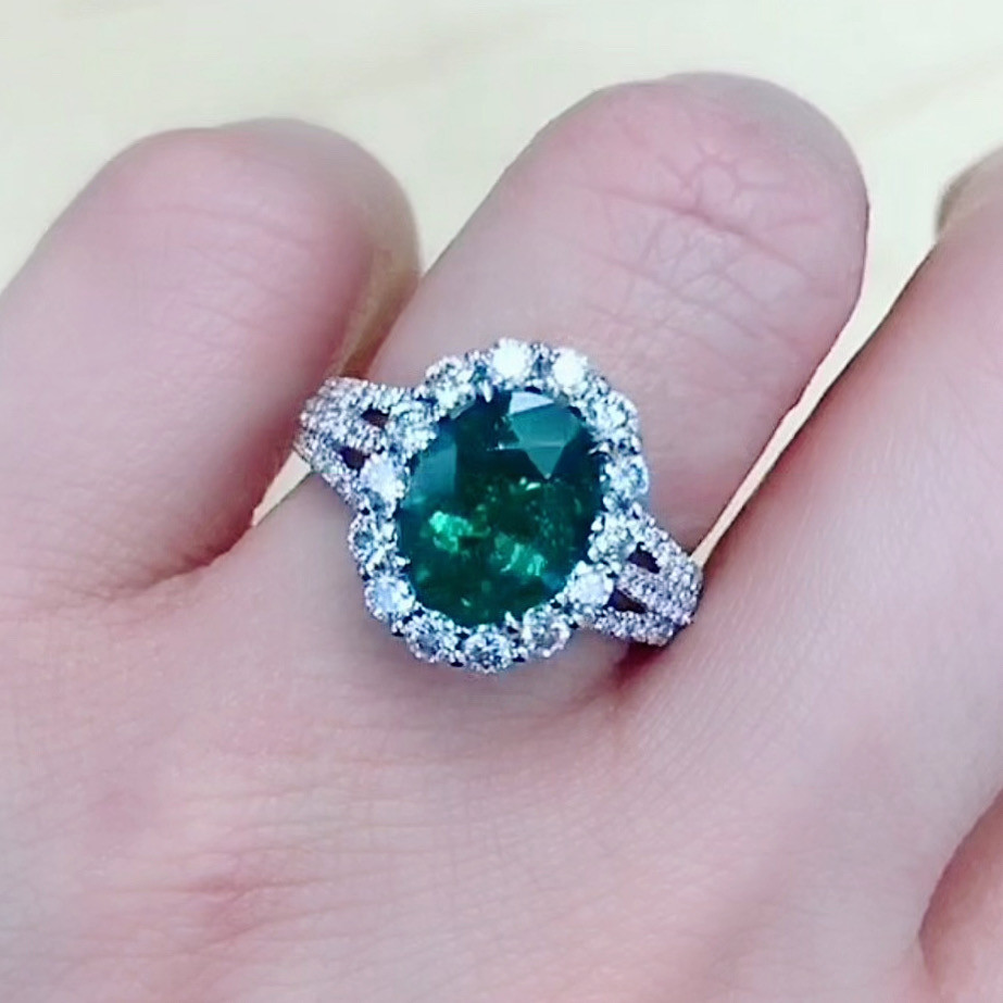 lady's hand wearing a large oval emerald and diamond cocktail ring engagement ring vintage inspired white gold ring with split shank