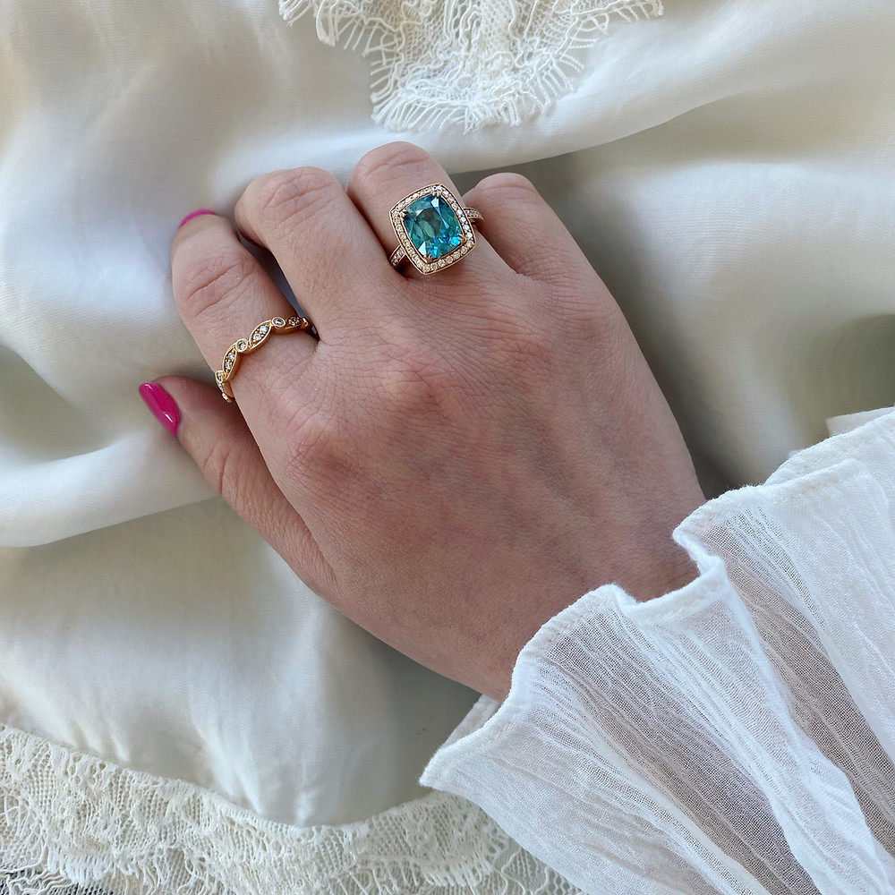Woman's hand wearing a large rose gold and blue zircon cocktail ring and stacking ring