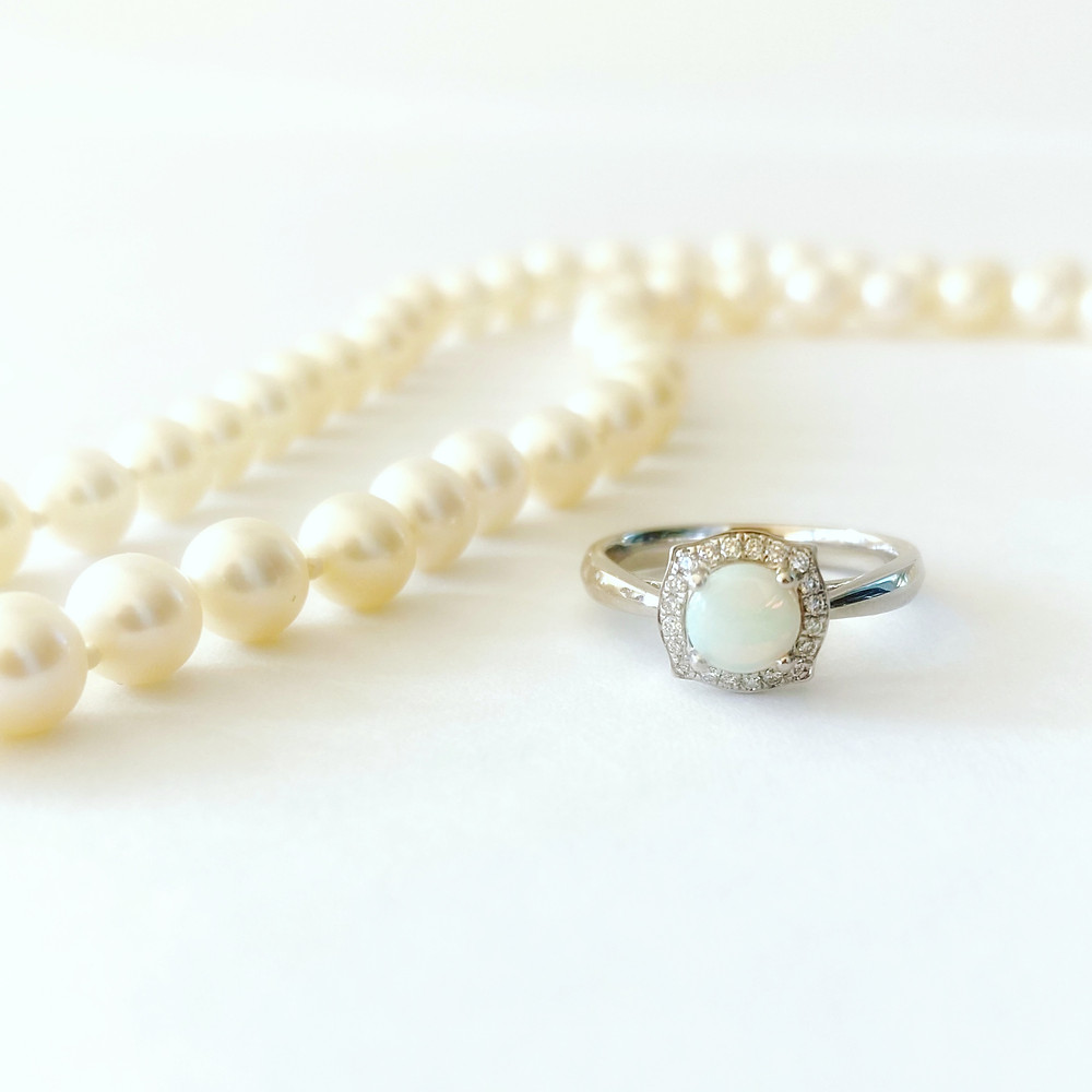 round opal, vintage inspired, white gold, diamond halo engagement ring, next to a strand go white pearls on a white background