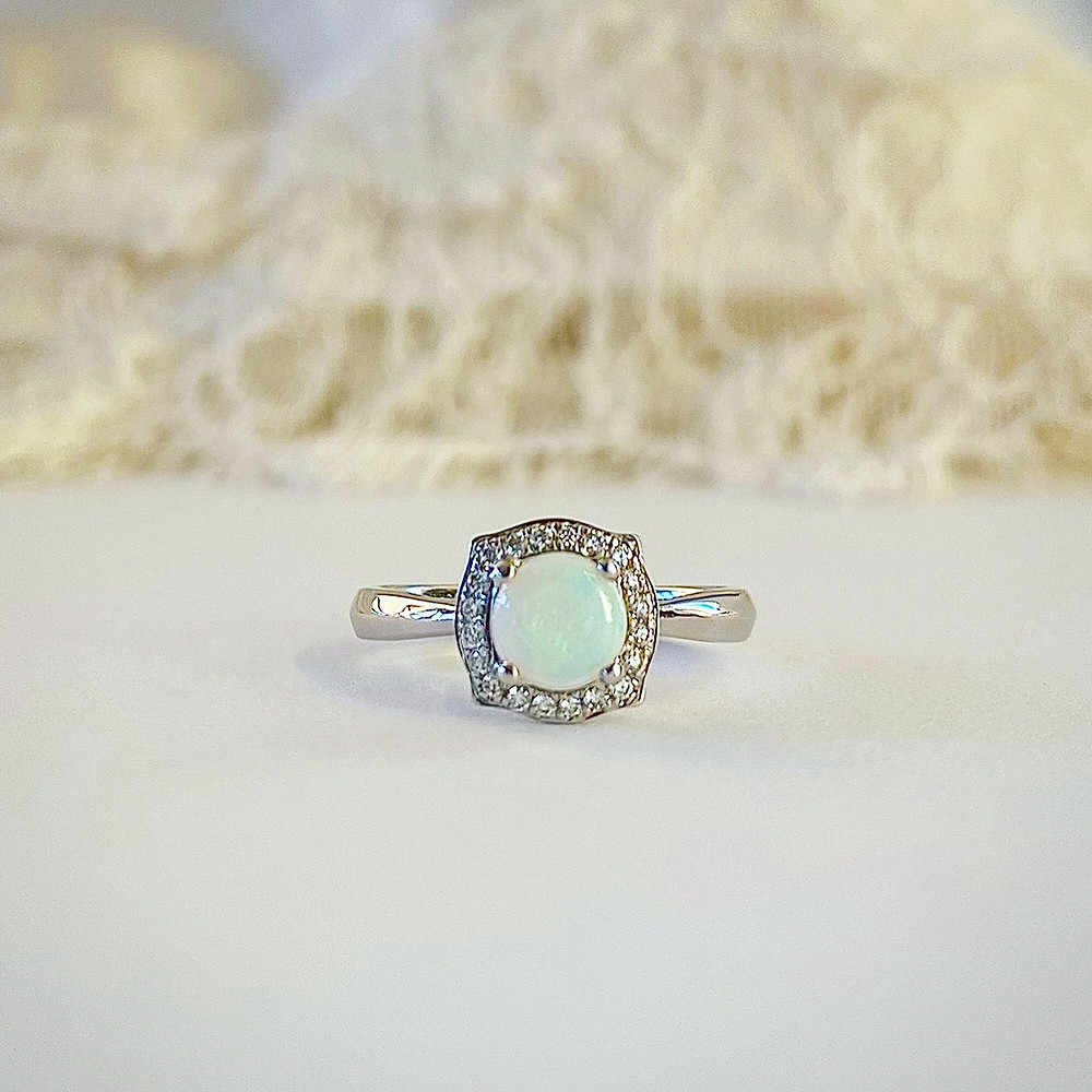 round white opal set in white gold ring with vintage inspired cushion halo with natural diamonds on white and lace background by Tsarina Gems