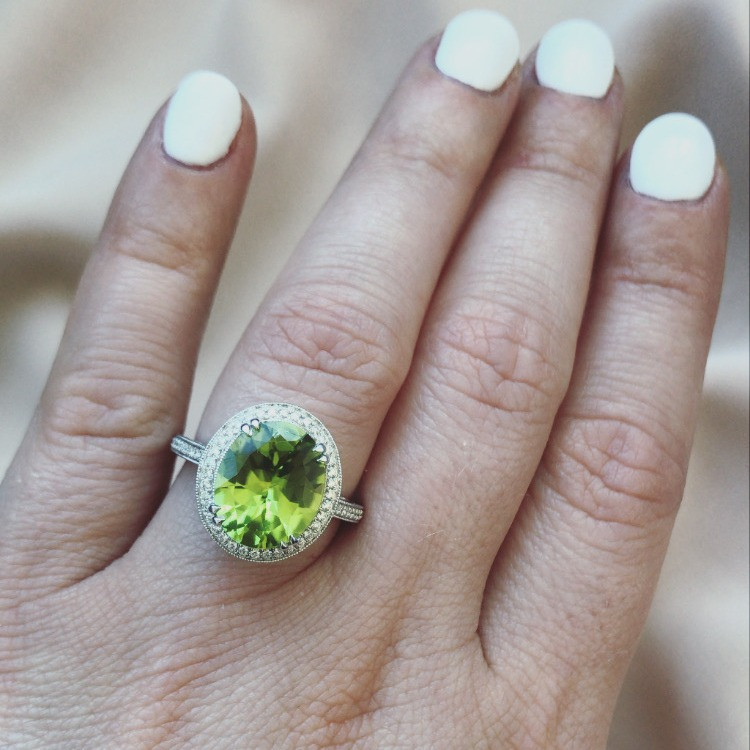 Lady's hand wearing a large oval peridot and diamond halo white gold cocktail ring on her ring finger