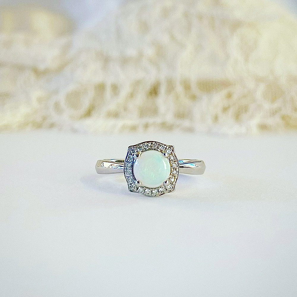 a round opal and diamond halo white gold ring on a white silk background